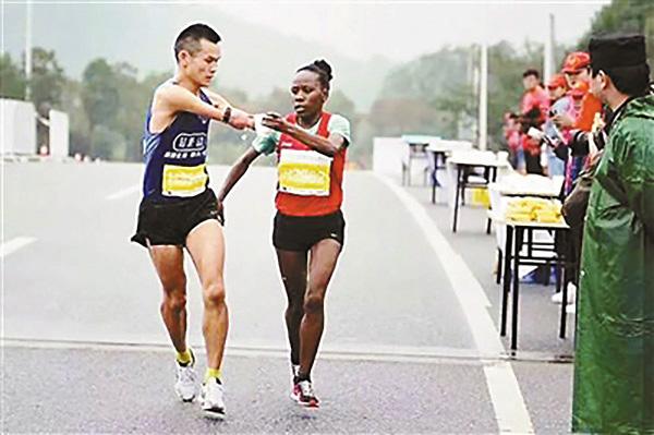 10月15日,安徽池州马拉松赛埃塞俄比亚女选手为任耀递水。北京青年报 图