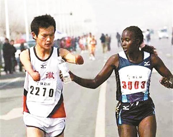 7年前的马拉松赛外籍选手给任耀递水。北京青年报 图