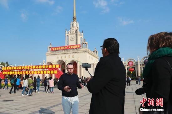 """10月16日,来自拉美、海湾等地域的多个记者团在北京观光""""砥砺奋进的五年""""大型成就展。 中新社记者 盛佳鹏 摄"""