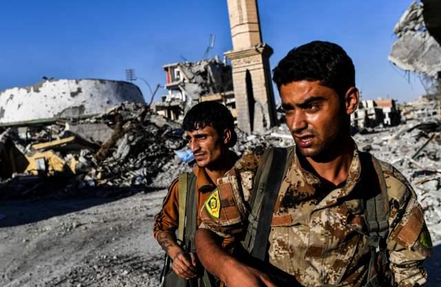 """10月16日,""""叙利亚民主军""""成员查看拉卡体育场周边区域。(新华/法新)"""