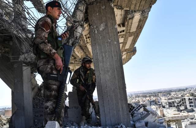 """10月16日,""""叙利亚民主军""""成员登上拉卡一座建筑查看周边区域。(新华/法新)"""