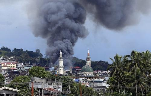 资料图:6月27日,在菲律宾南部棉兰老岛马拉维市,一处遭空袭地点升起浓烟。新华社发