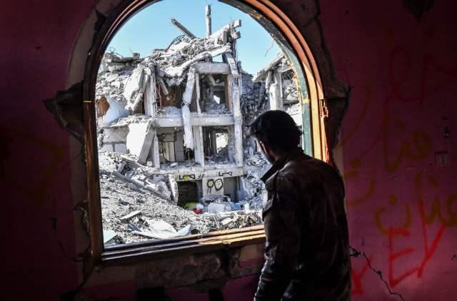 """10月16日,一名""""叙利亚民主军""""成员在拉卡一座建筑内向外望。(新华/法新)"""
