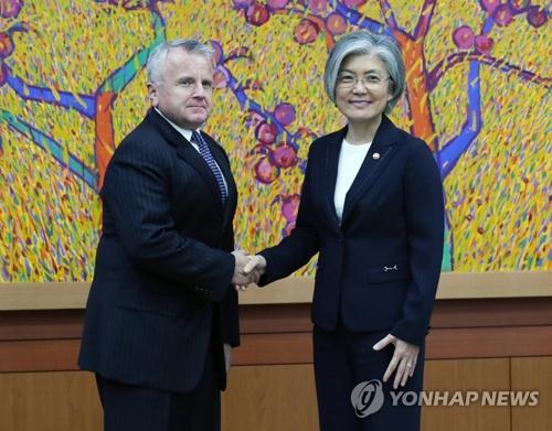 10月18日,在首尔外交部大楼,韩国外交部长官康京和(右)与美国国务院副国务卿约翰·沙利文握手合影。(韩联社)