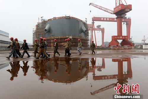 图为江苏泰州一家造船厂内,工人从正在建造的船前经过。(资料图片)中新社记者 泱波 摄