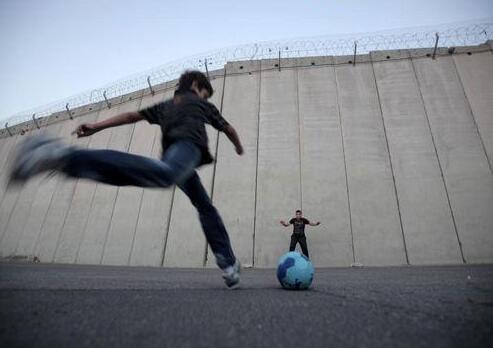 资料图:巴勒斯坦儿童在以色列隔离墙附近玩耍。