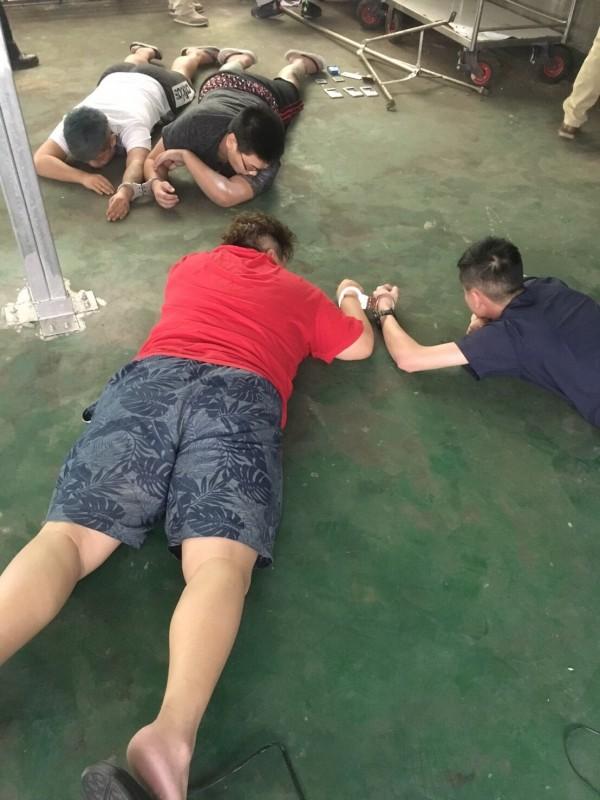 以苏姓嫌犯为首的诈骗集团成员被控制在地上。