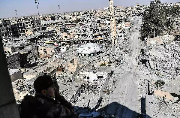 """一名""""叙利亚民主军""""成员10月16日在拉卡一座建筑内监视周边区域。新华社/法新"""