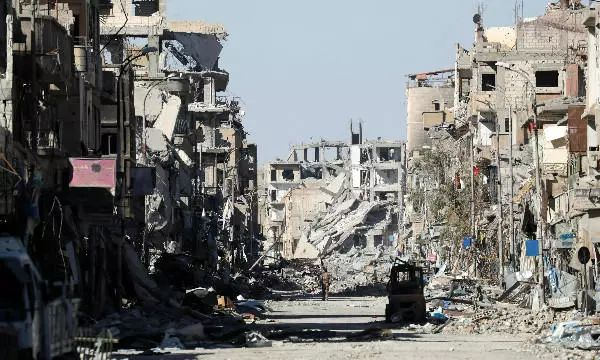 """一名""""叙利亚民主军""""士兵10月18日行走在拉卡废墟中。新华社/路透"""