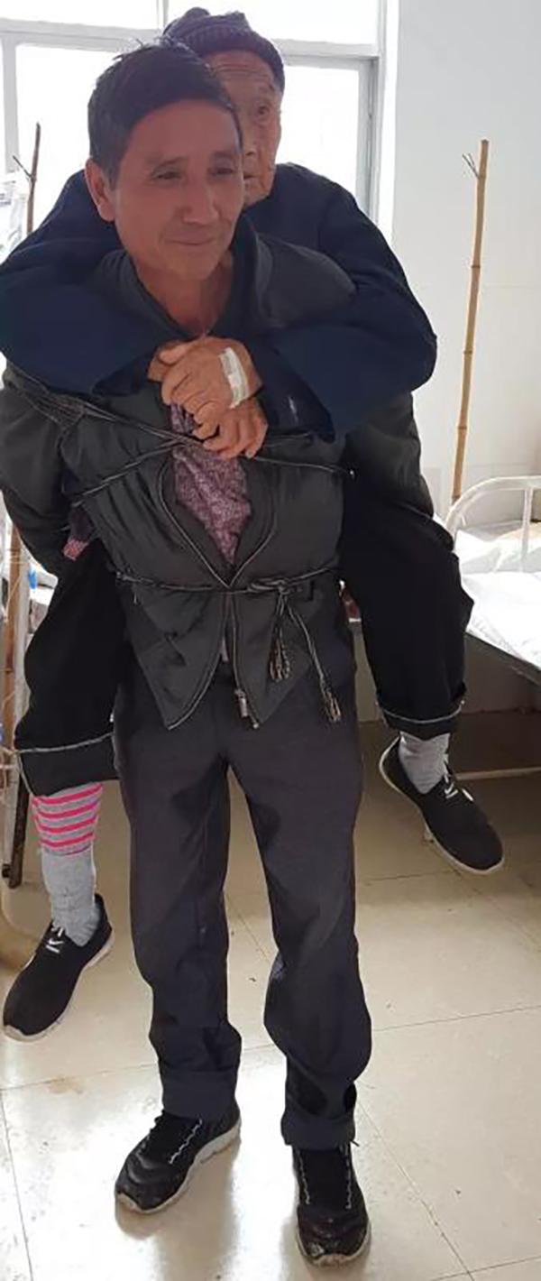 治疗完之后,他又用背带包裹背起母亲,准备离开村卫生室。刘苏瑶 图