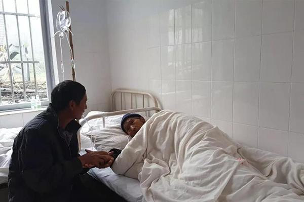母亲躺在病床上输液,汪克武守候在旁紧握着母亲的手。刘苏瑶 图