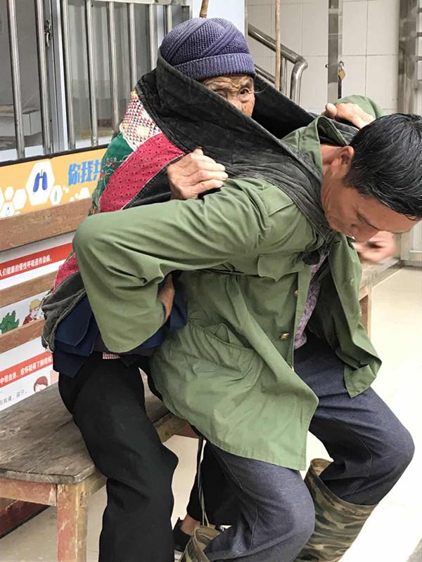 背到村卫生室门口,汪克武让母亲坐一张板凳上准备解绳子。张晓瑜 图