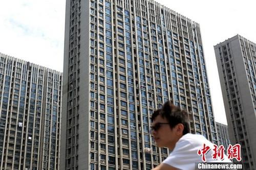 资料图:市民从南京一处楼盘前经由。中新社记者 泱波 摄