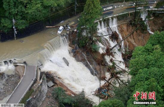 """当地时间10月23日,日本岸和田市一条公路被暴雨冲毁。当日,强台风""""兰恩""""登陆日本列岛。"""