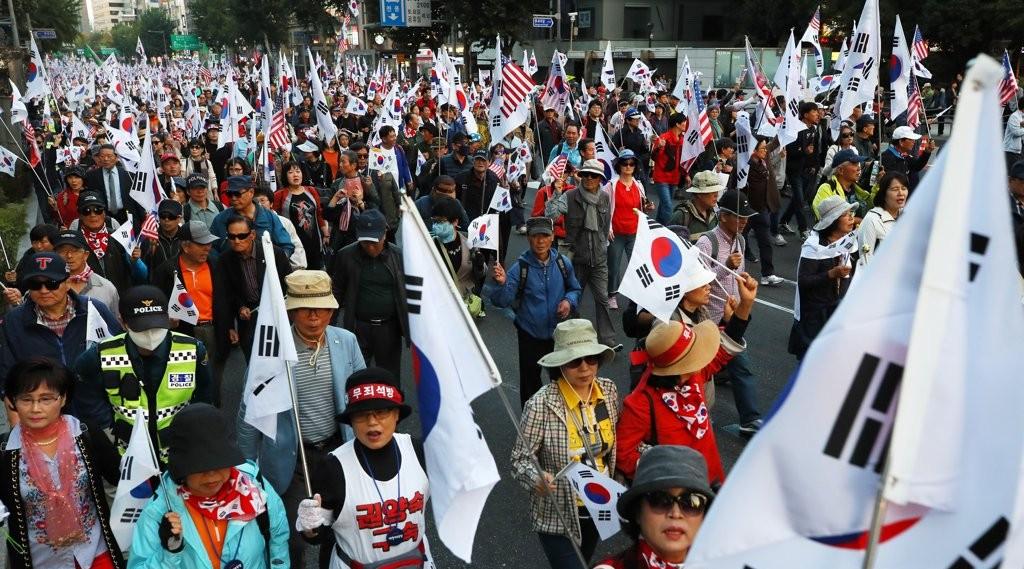 21日,韩国民众手挥太极旗与星条旗,呼吁释放朴槿惠
