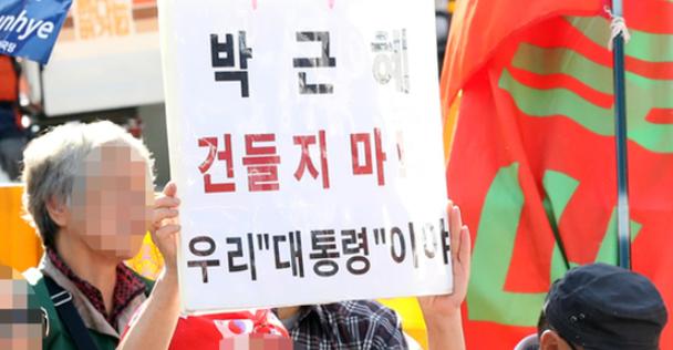 """21日,韩国民众手持标语""""别惹朴槿惠!"""""""