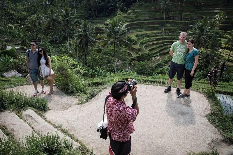 ▲巴厘岛上,一名导游正在为游客拍照。