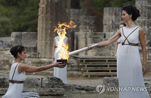 当地时间10月24日,扮演最高女祭司的希腊演员卡特里林娜·勒侯(右)点燃火种罐。(图片来源:韩联社)