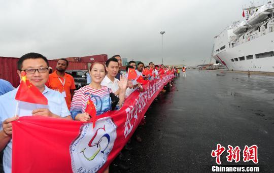 10月26日,安哥拉罗安达港码头,前来送行的中资企业员工挥舞中国国旗,送别中国水师宁静方舟医院船。山河 摄