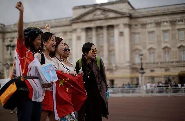 ▲几名中国女孩在英国伦敦白金汉宫前开心地举着国旗拍照。
