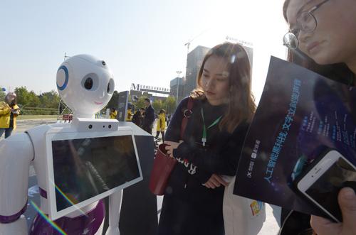 10月24日,在科大讯飞(首届)全球1024开发者节展示区内,观众在与智能语音机器人对话。新华社记者 郭晨 摄