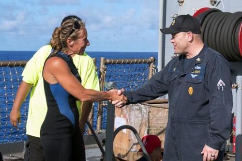 阿佩尔(左)和解救她的美国海军人员握手。图片来源:美国海军