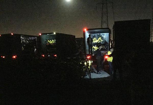 箱式货车正在装运单车,一名身着黄色OFO制服的工作人员正来回帮忙。