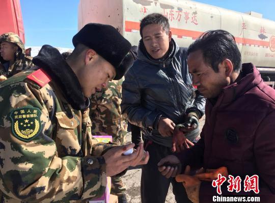 武警兵士正在为受困大众发放救灾物质。武警那曲支队供图