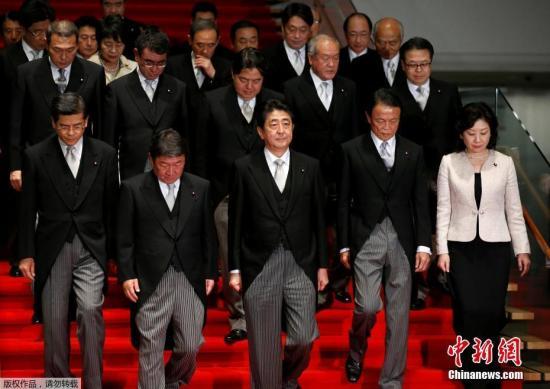 资料图:日本首相安倍晋三(前排中)带领阁僚合影。