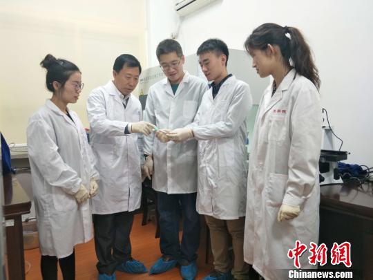 论文第一作者张伟副教学(左三)跟吴承伟教学(左二)在领导研讨生做试验。 姚璐 摄