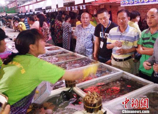 图为三亚某海鲜加工广场,前来购置海鲜的主顾川流不息。(材料图片,图文有关) 尹海明 摄
