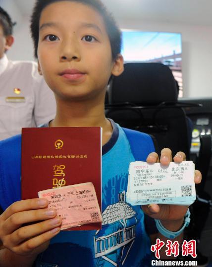 刘浩钦展示前往北京和上海参观铁路博物馆的车票。 蒋雪林 摄