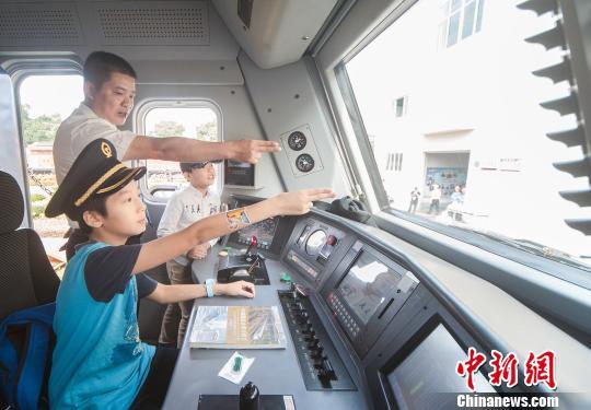刘浩钦在机车内学习火车司机的手势。 蒋雪林 摄