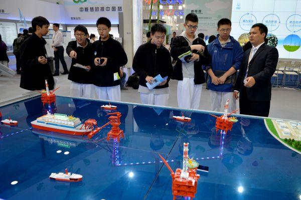 资料图片:2014年4月17日,几名北京三十五中的同学在展览会上参观由中国核工业集团公司研发的浮动式核电站模型。新华社记者 李鑫 摄