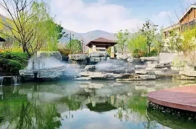 露天的池子往山石茅屋及其灌木丛中,藏匿着一片静幽与迷离。云烟缭绕,热气氤氲,汪汪碧水在青山绿树的映衬下显得格外诱人。