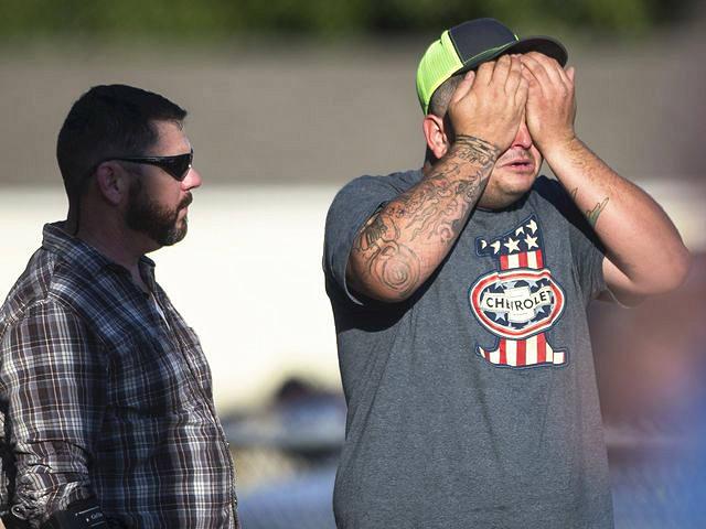 萨瑟兰斯普林斯镇,一名男子双手捂脸擦拭着眼泪。(新华/美联)