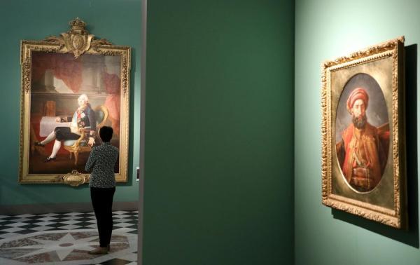 一位观众在凡尔赛举办的《凡尔赛的游客》临展中观赏一幅路易十六的肖像。