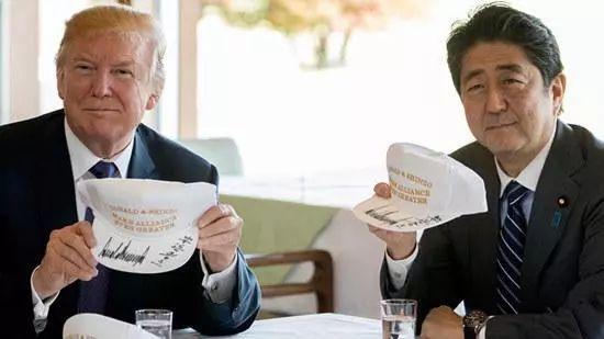 """▲安倍与特朗普展示了印有""""Donald & Shinzo Make Alliance Even Greater""""(唐纳德和晋三使同盟更伟大)字样的帽子。"""