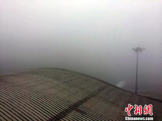 乌鲁木齐国际机场批示塔台下年夜雾洋溢。 陶卉 摄