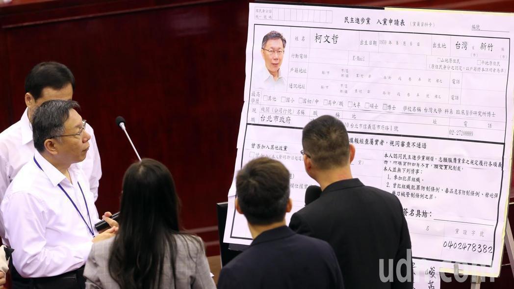 """民进党籍台北市议员洪健益等人拿出""""入党申请表""""邀请柯文哲(左)现场加入民进党。(图片来源:台湾《联合报》)"""