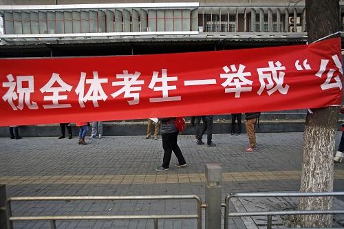 资料图片:2015年11月29日,考生在北京市实验职业学校考点外复习,一家考试辅导机构的宣传横幅挂在附近的树上。新华社记者 沈伯韩 摄