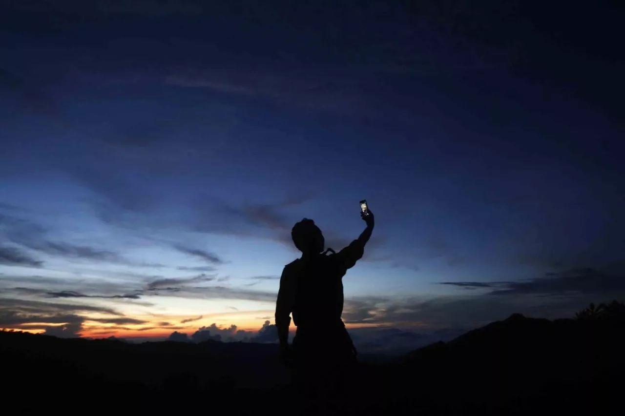 阿超在山顶费力寻找信号。