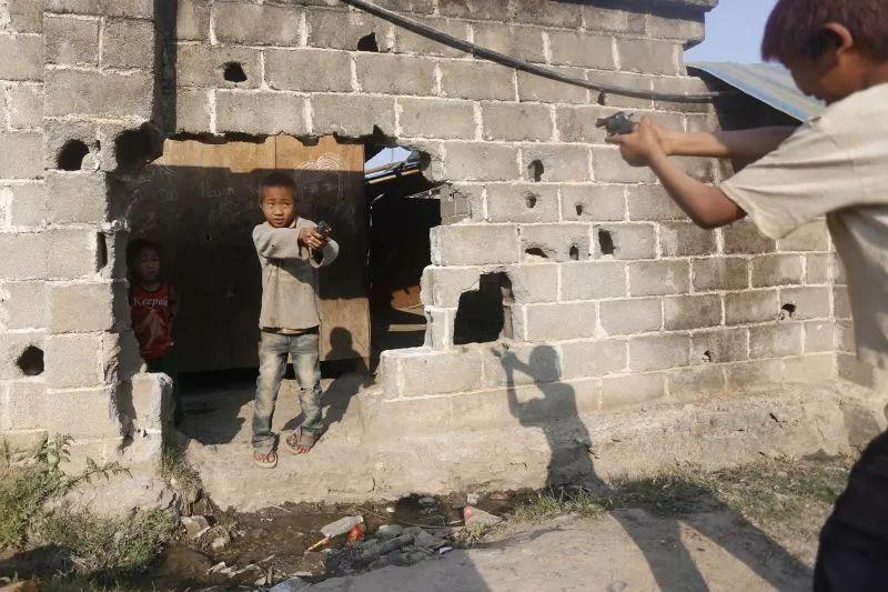 孩子们在难民营中玩着游击队游戏。