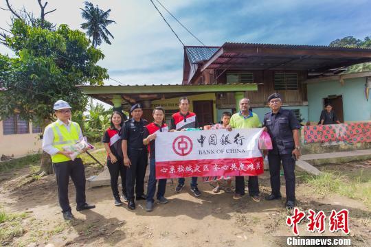 马来西亚中资企业协会会长、马来西亚中国银行行长王宏伟(中)日前代表中资企业协会前往槟州灾区看望灾区民众并送去灾区急需物品。 赵胜玉 摄
