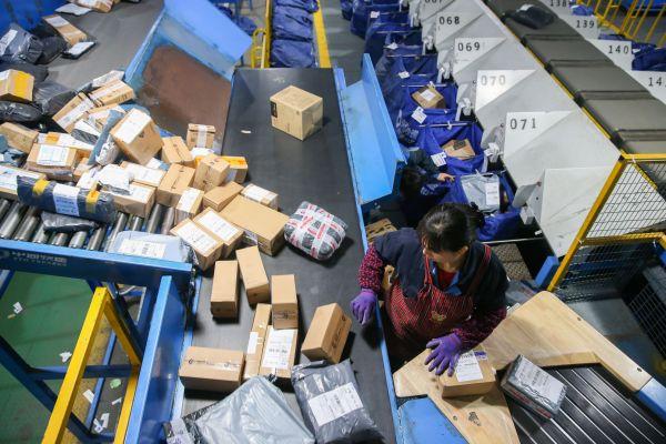"""11月11日,在中通快递上海分拨中心,工作人员在流水线上工作。 当日,一年一度的""""双十一""""拉开序幕,各家快递企业全员上阵应对大量网购订单带来的快递高峰,确保物流畅通。 新华社记者 丁汀 摄"""