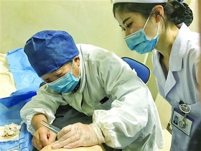 77岁的李琦仍坚持为病人换药 /晨报记者 张益维