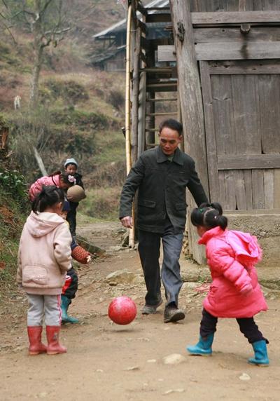 周宏军是广西融水苗族自治县汪洞乡新合村达佑屯教学点唯一的教师。2012年3月13日,周宏军领着孩子们踢足球。视觉中国供图(资料图片)