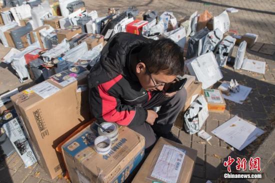 11月13日,山西太原高校校园内,快递公司在一片空地上按序堆满快件,等待大学生前来领取。 韦亮 摄