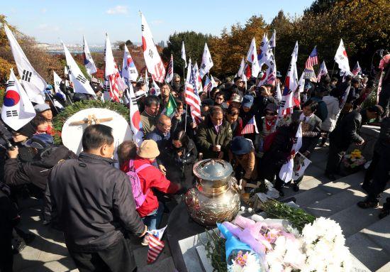 14日,韩国民众手挥太极旗星条旗参加纪念活动