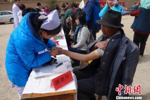 资料图:医疗志愿服务队对当地群众测量血压。 孙睿 摄
